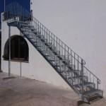 Escalera de hierro con peldaños emparrillados