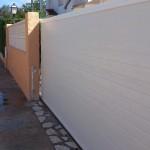 Porta de parcel·la corredissa amb panel acanalat