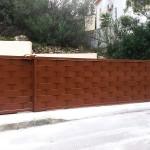 Porta de parcel·la corredissa de ferro amb xapa galvanitzada i lacat color marró