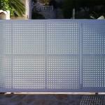 Porta de parcel·la amb xapa perforada i lacat blanc