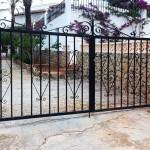 Porta de parcel·la abatible de ferro amb decoració de forja