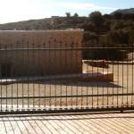 Porta de parcel·la corredissa de ferro amb decoració