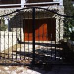 Porta de parcel·la abatible de ferro amb decoració