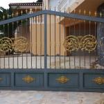 Porta de parcel·la abatible de ferro amb decoració i sòcol de xapa