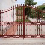 Porta de parcel·la abatible amb sanefa i corba