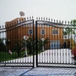 Porta de parcel·la abatible de ferro amb decoració i forma corba