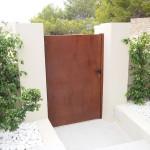 Porta peatonal de xapa cega amb aspecte de ferro oxidat