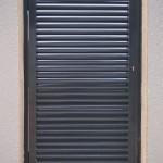 Porta peatonal semicega amb lames mallorquina lacada al forn color gris