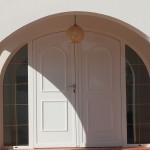 Porta amb arc de PVC color blanc amb panel decoratiu y vidre amb barrot dorat