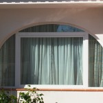 Finestra amb arc de PVC color blanc i vidre amb barrot dorat