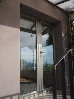 Porta abatible de dos fulles amb rotura tèrmica acabat anoditzat acer inox i doble acristalament