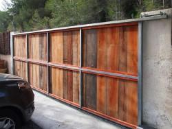 Porta de parcel·la corredissa. Estructura de ferro i madera natural