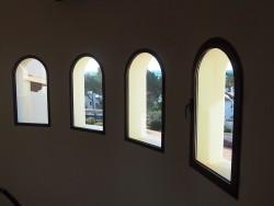 Vista interior de fijos y ventana con curva en aluminio color madera